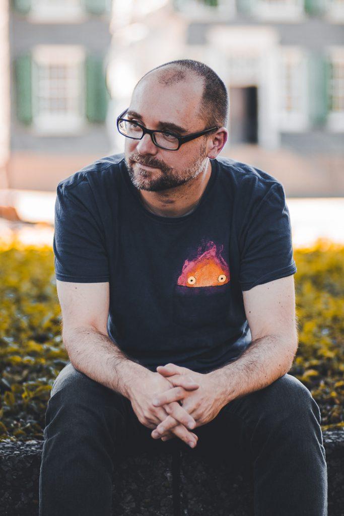 Ein Mann mit Brille und Bart sitzt vor einem nur verschwommen wahrnehmbaren Haus.